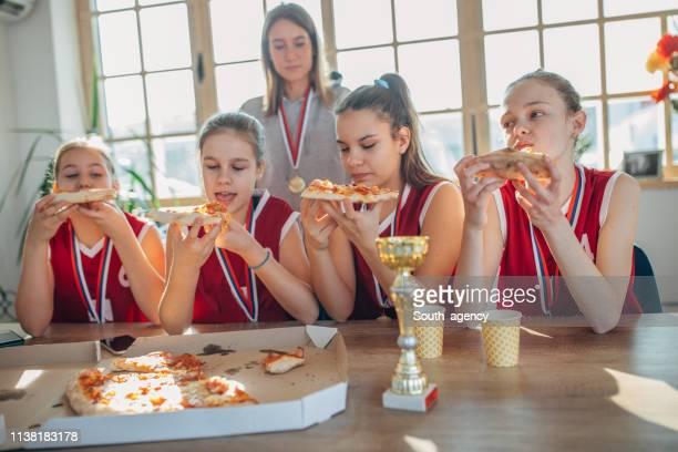 jogadores de basquetebol das meninas que comem a pizza com ônibus após wining um troféu - trophy - fotografias e filmes do acervo