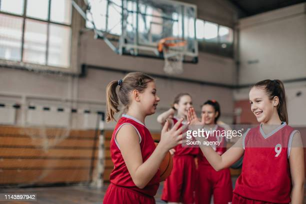 girls basketball players handshake on court after match - sports league stock pictures, royalty-free photos & images