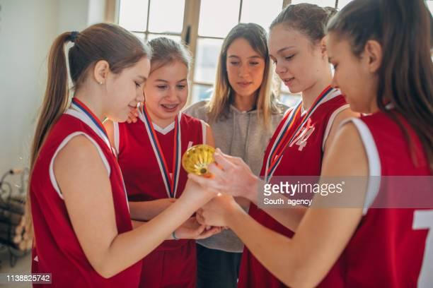jogadores de basquetebol das meninas que prendem um troféu de vencimento com o ônibus em casa - trophy - fotografias e filmes do acervo