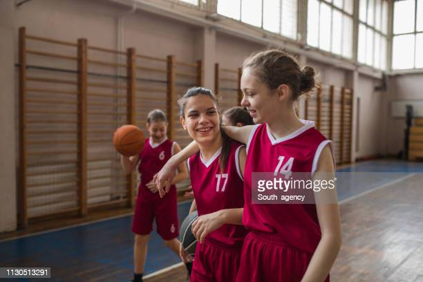 girls basketball players hugging on court after match - basketball competition stock pictures, royalty-free photos & images