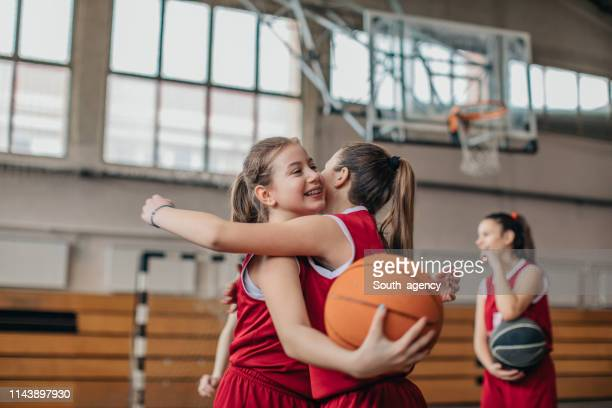 girls basketball players hugging on court after match - sports league stock pictures, royalty-free photos & images