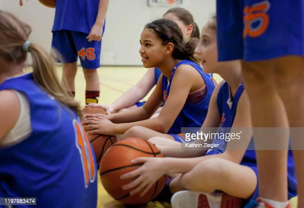 girls' basketball team sitting together before training - basketbal teamsport stockfoto's en -beelden