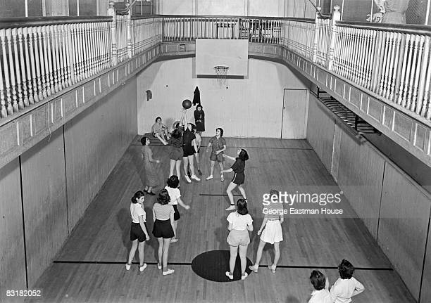 Girls battle for the basketball after a jumpball has been tossed by the referee during a game in an indoor gymnasium United States ca1920s