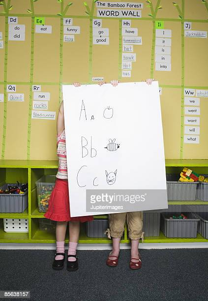 Girls behind posterboard