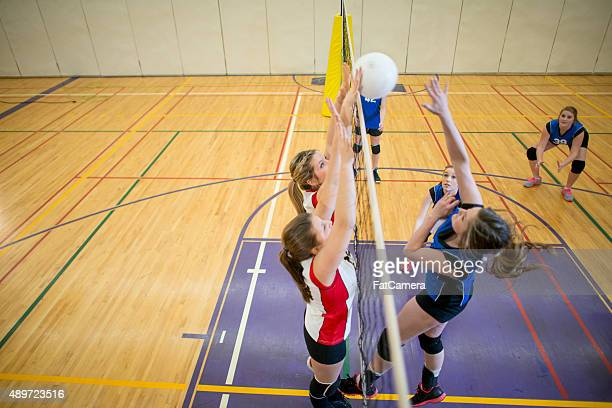 girls blocking a volleyball shot - high school volleyball stock photos and pictures