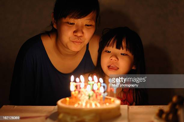 Girls blowing birthday cake's candles