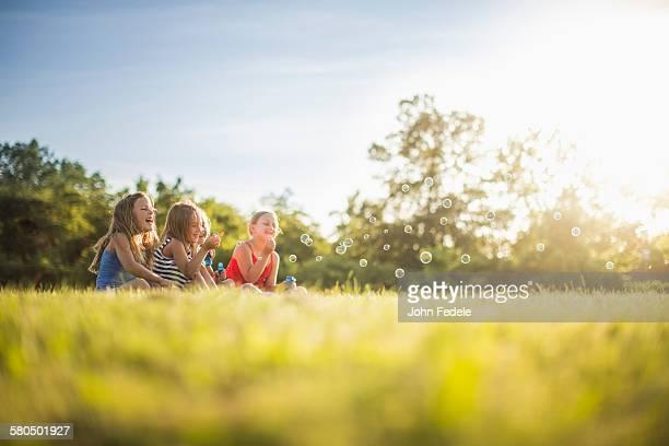 Girls blowing bubbles in grass field