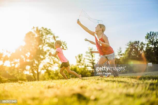 Girls blowing bubbles in grass field