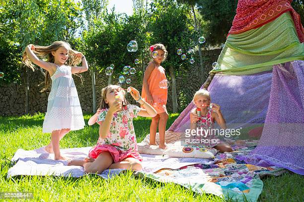 girls blowing bubbles in summer garden party - teepee stock pictures, royalty-free photos & images