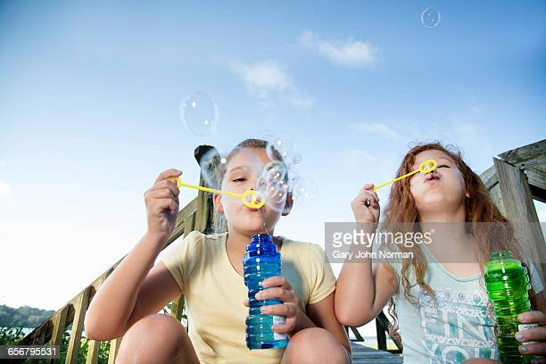 Girls blowing bubbles outdoors