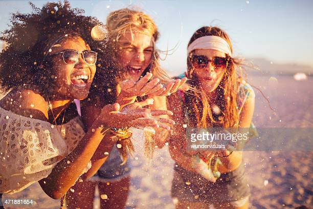 girls blowing confetti from their hands on a beach - tienermeisjes stockfoto's en -beelden