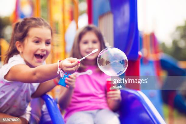 Girls Blowing Soap Bubbles at the Park