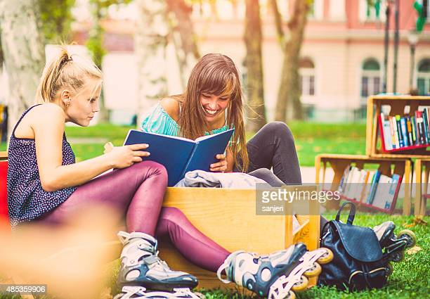Girls bonding together and reading book at the city park