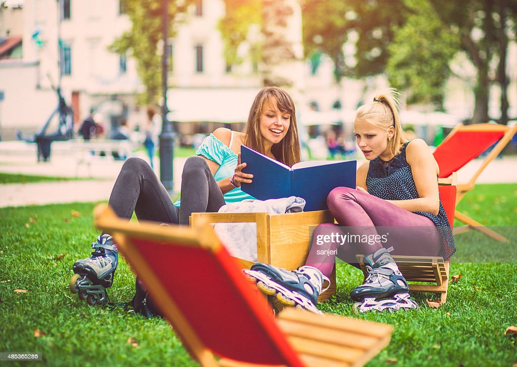 Girls Bonding Together And Reading Book At The City Park High-Res Stock Photo - Getty Images