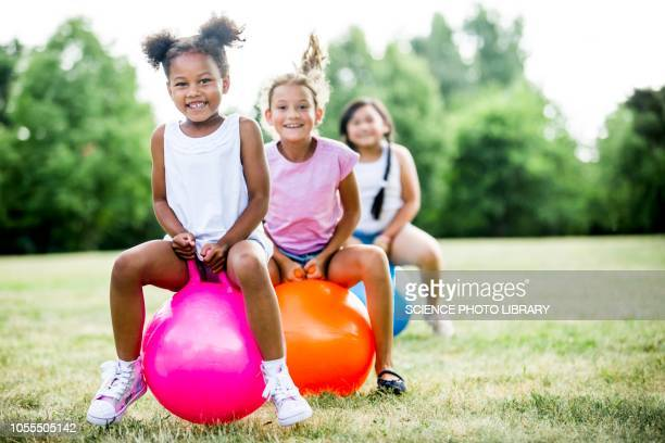 girls bouncing on inflatable hopper - hoppity horse stock photos and pictures
