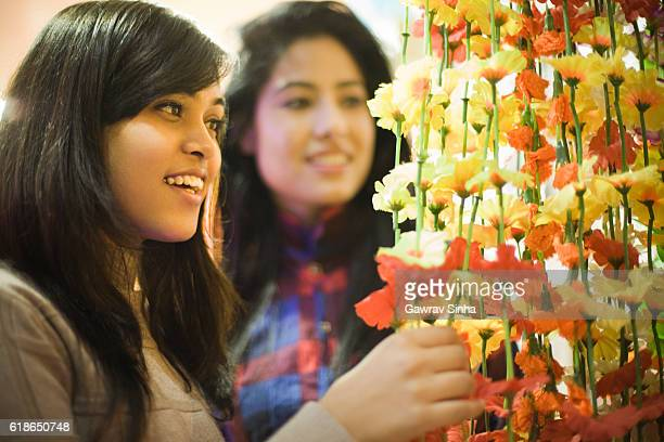 Girls buying floral wall hanging in decor shop before festival.