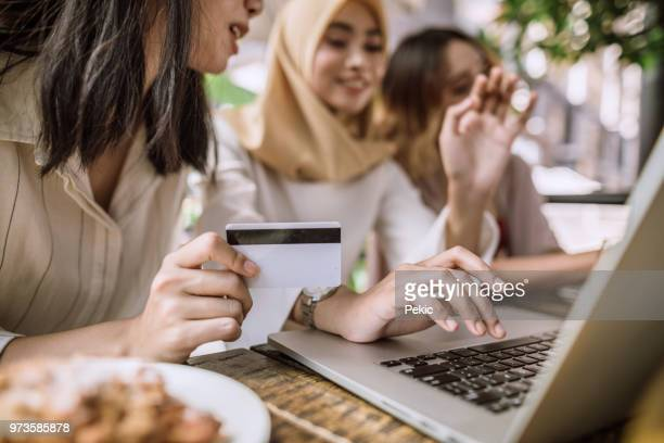 girls buying online while having lunch outdoors - malaysian culture stock pictures, royalty-free photos & images