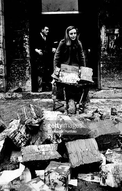Girls carrying on a wheelbarrow the documents of the Museum of the History of Science today Museo Galileo damaged during the flood of the Arno River...