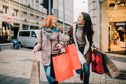 Girls carrying shopping bags 1073935306
