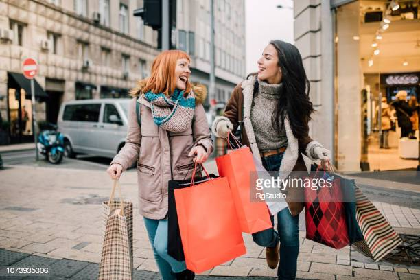girls carrying shopping bags - girls stock pictures, royalty-free photos & images