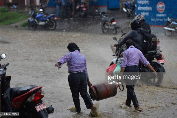 Girls carrying the cooking gas on the heavy rain at Kathmandu Nepal on Sunday June 03 2018