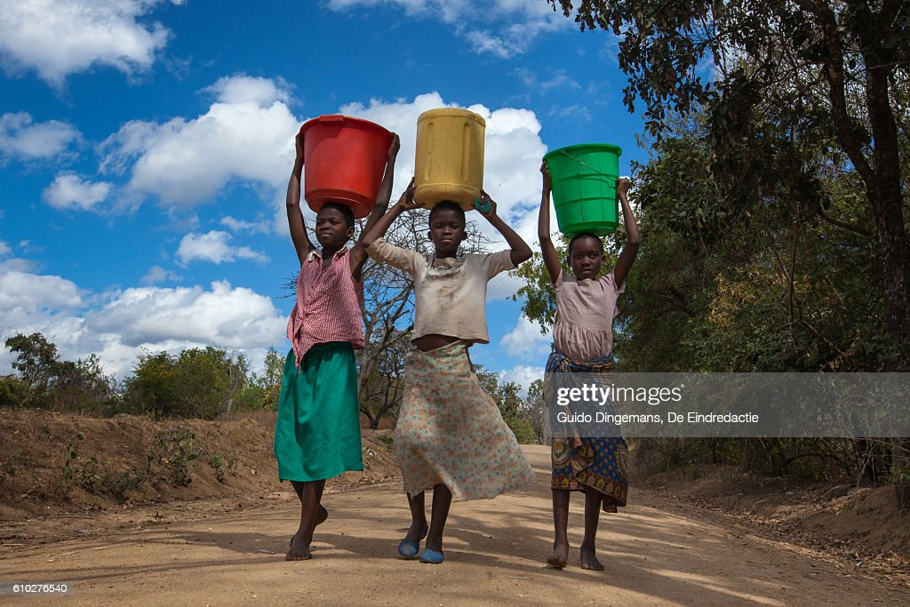 Girls carrying water buckets at a borehole in Malawi : Stock Photo