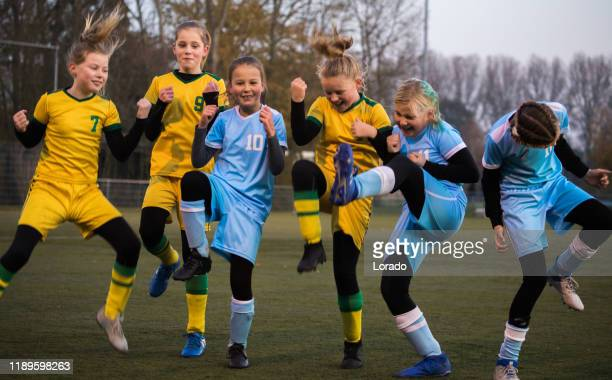girls celebrating a goal during a football match - team sport stock pictures, royalty-free photos & images