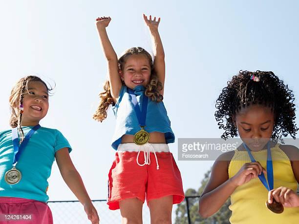 Girls celebrating on winners podium (low angle view)