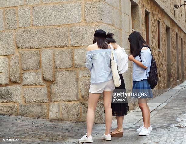 Girls chatting from the smartphone in the middle of the street