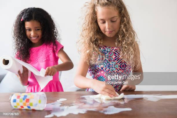 Girls cleaning spilled milk on table