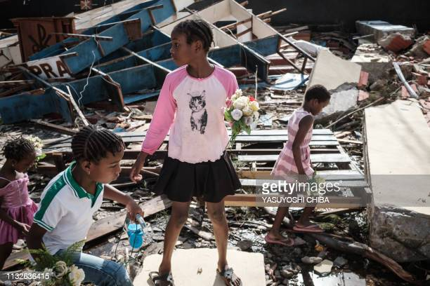 Girls collect artificial flowers from the rubble of a building destroyed by the cyclone Idai at Sacred Heart Catholic Church in Beira Mozambique on...
