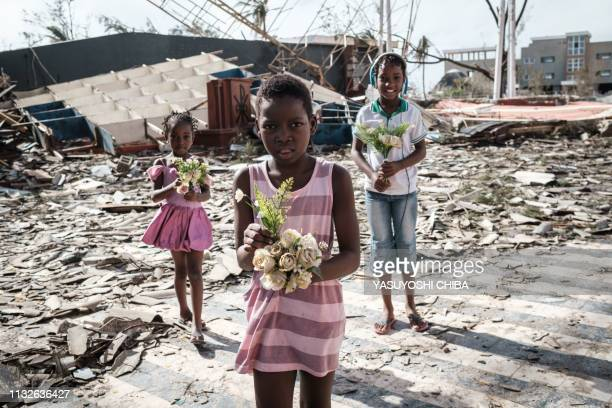 TOPSHOT Girls collect artificial flowers from the rubble of a building destroyed by the cyclone Idai at Sacred Heart Catholic Church in Beira...