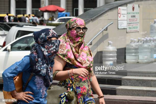 Girls cover their face to protect themselves from the scorching sun and heat waves on a hot summer day at Connaught Place on June 7 2018 in New Delhi...