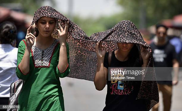 Girls cover their faces to protect themselves from scorching heat on a hot summer day on May 19 2016 in New Delhi India Heat waves hit north India...
