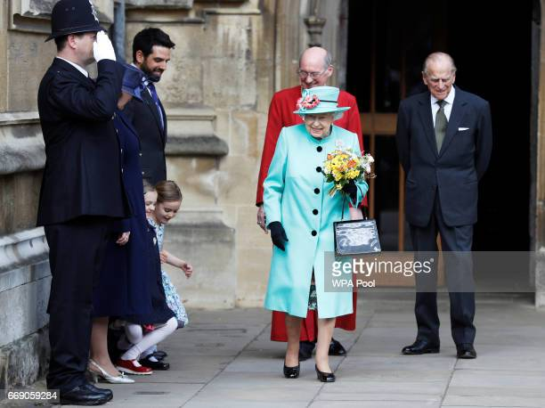 Girls curtsey as Queen Elizabeth II and Prince Philip Duke of Edinburgh leave the Easter Day service at St George's Chapel on April 16 2017 in...