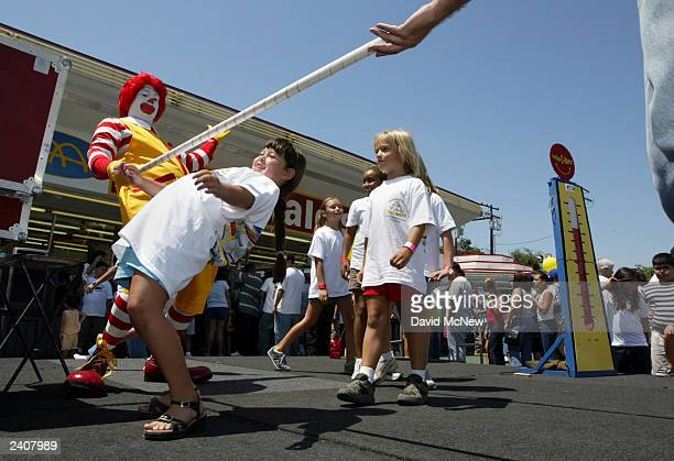 Girls dance the limbo with the Ronald McDonald mascot clown at the world's oldestoperating McDonald's fast food restaurant on its 50year anniversary...