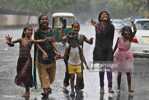 Girls dancing and enjoying the pre monsoon rain near Bal Bhawan on June 14 2013 in New Delhi India The city received 116 mm rainfall and the humidity...
