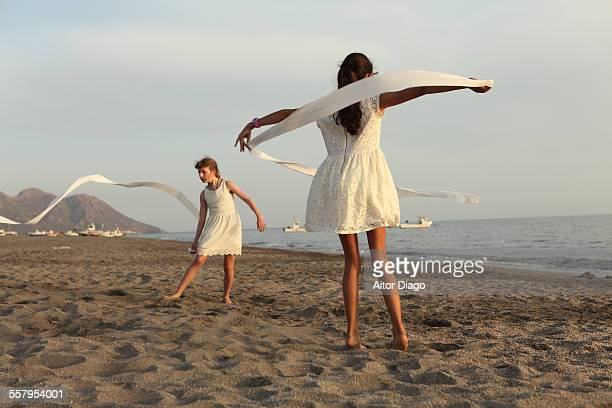 Girls dancing ballet in white clothes at the beach