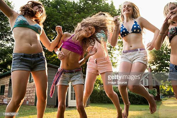 girls dancing in garden - swimwear stock photos and pictures