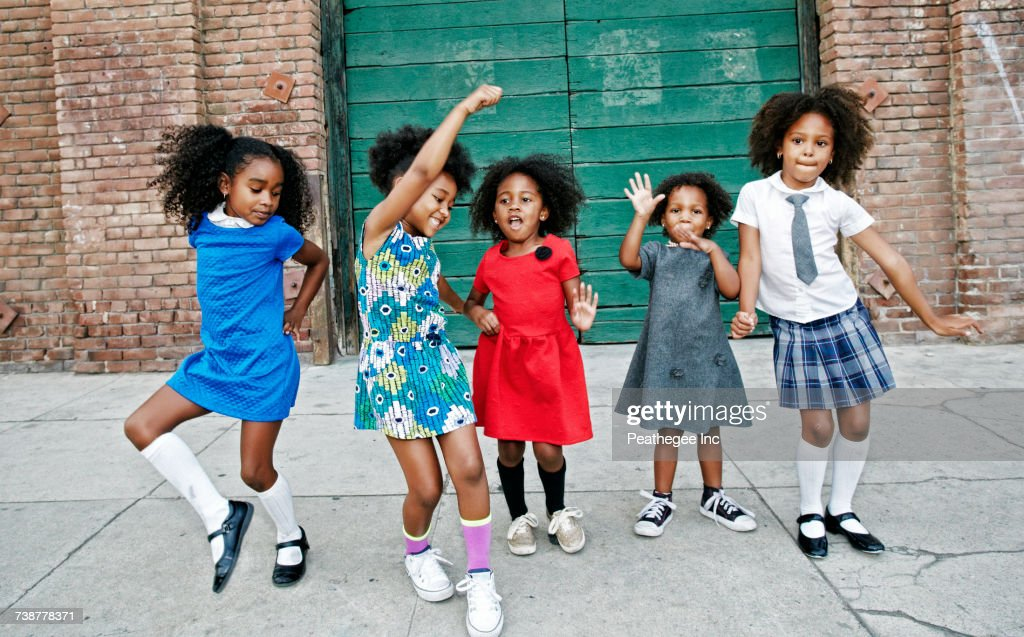 Girls dancing on city sidewalk : Stock Photo