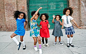 Girls dancing on city sidewalk