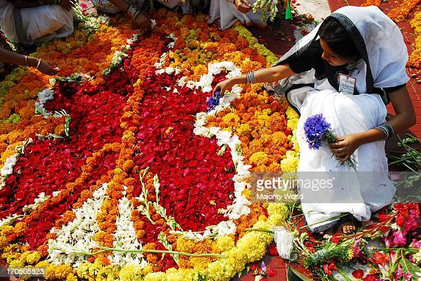 Girls decorate flowers at Central Shahid Minar Central Shahid Minar at Dhaka covered with flowers on the eve of International Mother Language Day On...