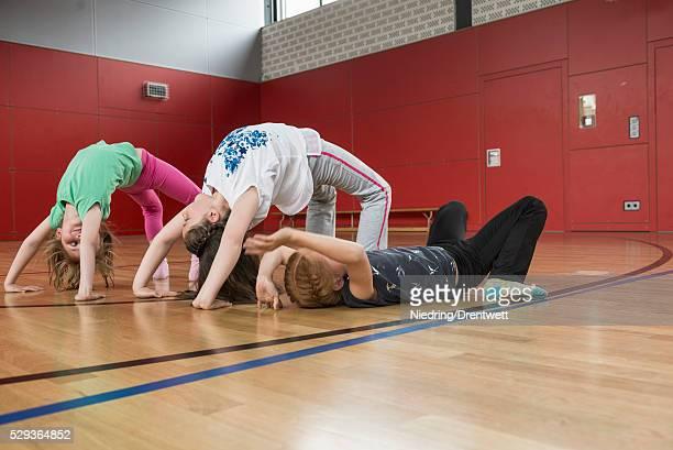 Girls doing bridge position yoga in sports hall, Munich, Bavaria, Germany