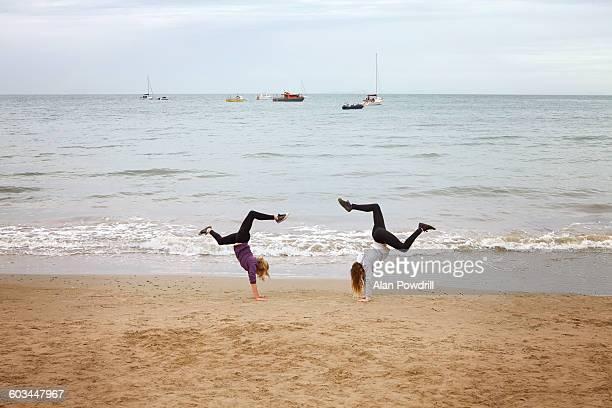 2 girls doing hand stands on beach