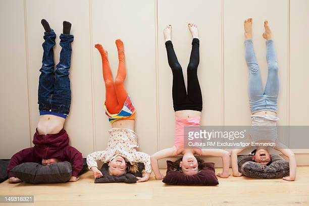 Girls doing headstands against wall
