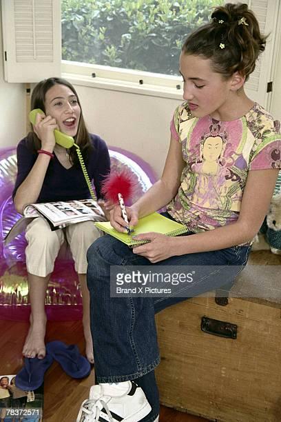 Girls doing homework and talking on telephone