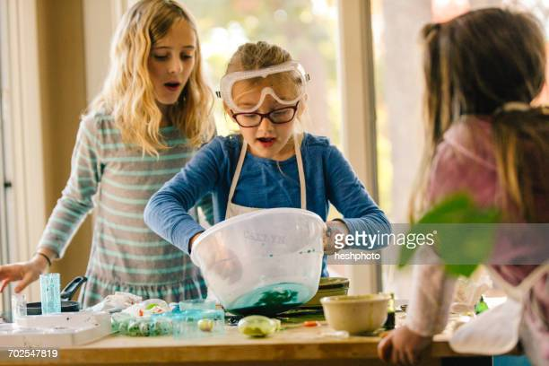 girls doing science experiment, mixing green liquid in bowl - heshphoto - fotografias e filmes do acervo