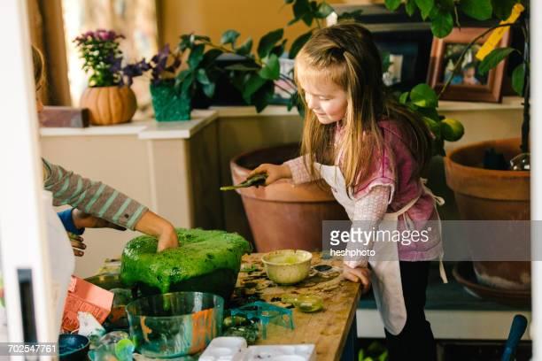 girls doing science experiment, with hand in green foaming liquid - heshphoto - fotografias e filmes do acervo