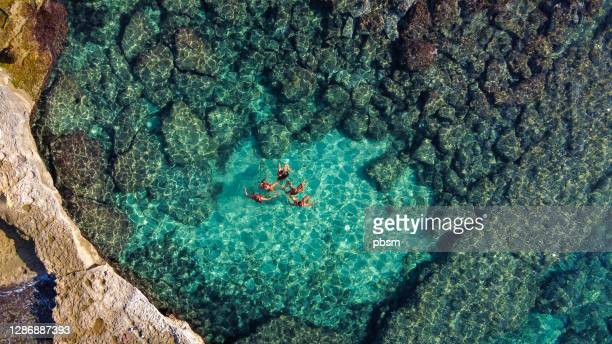 girls doing synchronized swimming at beach in majorca - balearic islands stock pictures, royalty-free photos & images