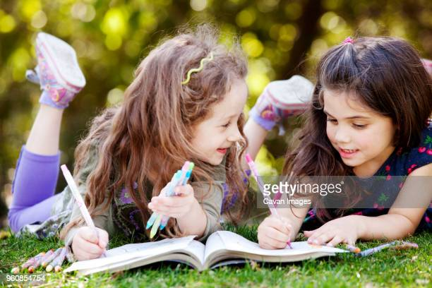 girls drawing on coloring book while lying on field - colouring book stock photos and pictures